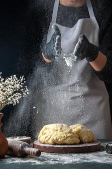 正面図女性料理人が暗い仕事で小麦粉で生地を広げている生の生地ホットケーキベーカリーパイオーブンペストリー