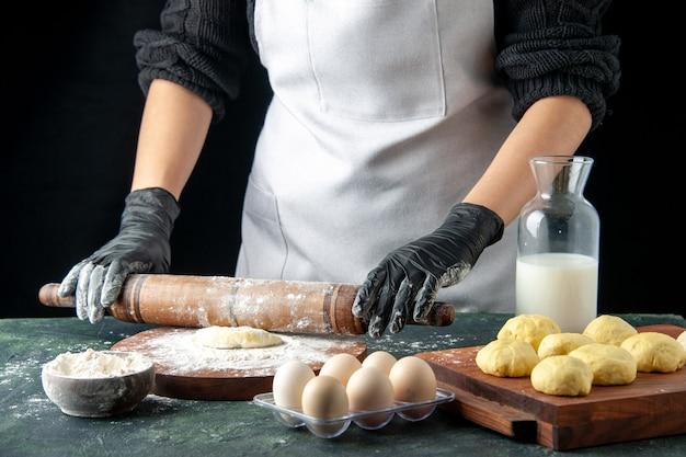 正面図女性料理人がダークケーキジョブオーブンで小麦粉と生地をロールアウトホットケーキ生地焼きパイ卵料理