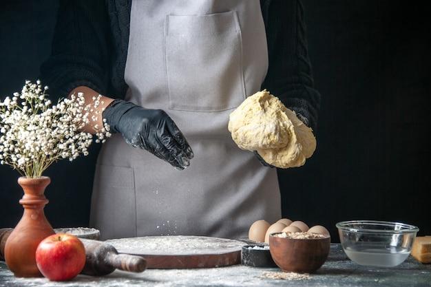 正面図女性料理人が暗い生地のペストリーキッチンのホットケーキ料理ベーカリーの卵に小麦粉で生地を広げています
