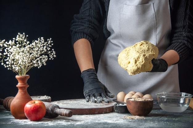 正面図女性料理人が暗い仕事の生地キッチンホットケーキ料理ベーカリー卵に小麦粉で生地を広げています