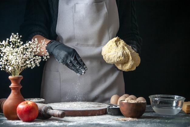Вид спереди женщина-повар раскатывает тесто с мукой на темной работе, тесто, тесто, горячие пирожные, кухня, выпечка, яйца, кухня