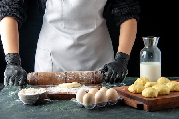 正面図女性料理人がダークケーキジョブオーブンで小麦粉と生地をロールアウトホットケーキ生地焼きパイ労働者卵料理
