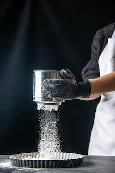 正面図女性料理人が暗いペストリーの仕事の卵ケーキパイベーカリー労働者料理の鍋に白い小麦粉をまく