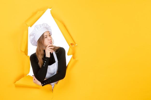 正面図女性料理人は黄色の感情の色の紙の仕事の料理の太陽の食べ物の写真を考えています