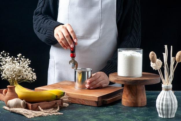 어두운 배경에 농축 우유 캔을 열려고 하는 전면 보기 여성 요리사