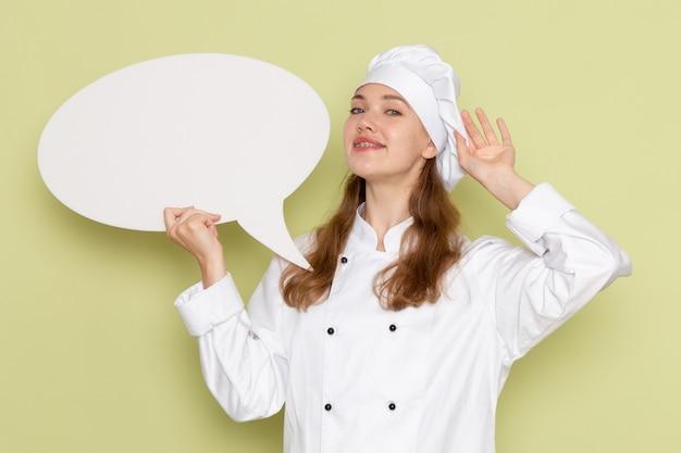 Vista frontale del cuoco femminile che indossa il vestito bianco del cuoco che tiene segno bianco e che sorride sulla parete verde