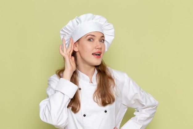 Vista frontale del cuoco femminile che indossa il vestito bianco del cuoco che prova a sentire fuori sulla parete verde