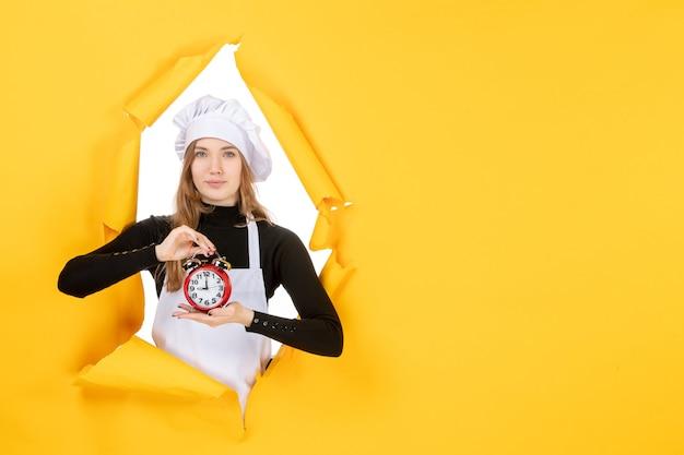 Cuoca vista frontale in berretto da cuoco bianco che tiene l'orologio sul colore giallo lavoro emozione cibo cucina cucina foto sole