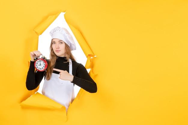 Cuoca di vista frontale in berretto da cuoco bianco che tiene l'orologio sul colore giallo lavoro emozione cibo cucina cucina sole