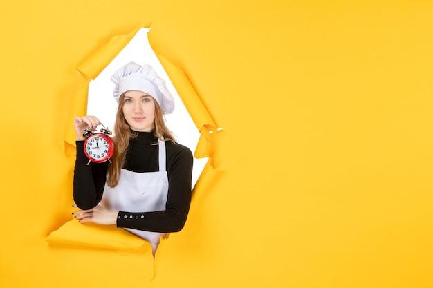 Cuoca di vista frontale in berretto da cuoco bianco che tiene l'orologio sul colore giallo lavoro emozione cibo cucina foto sole