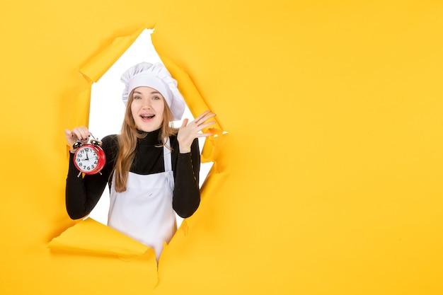 Cuoca vista frontale in berretto bianco cuoco con orologio su foto gialla lavoro cucina cucina cibo emozione