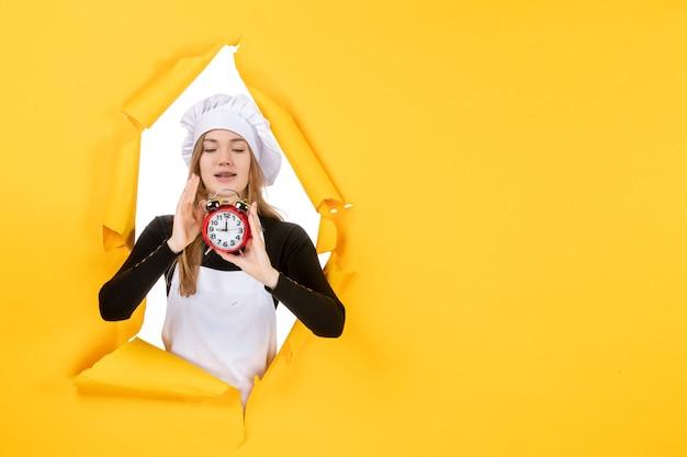 Cuoca vista frontale in berretto bianco cuoco con orologio su foto gialla lavoro cucina cucina sole emozione