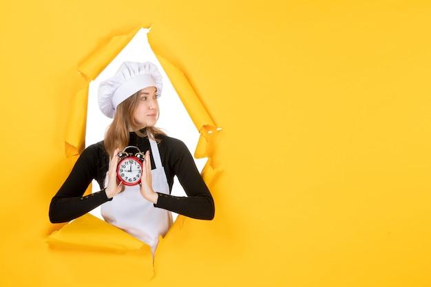 Cuoca vista frontale in berretto bianco da cuoco con orologio su foto gialla lavoro cucina cucina cibo sole emozione tempo