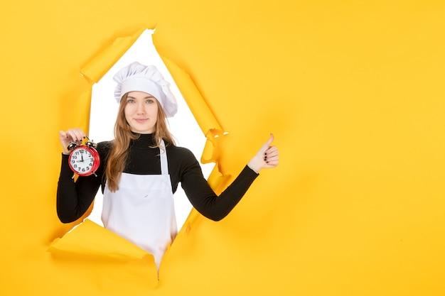 Cuoca vista frontale in berretto bianco cuoco con orologio su foto gialla lavoro cucina cucina cibo sole emozione