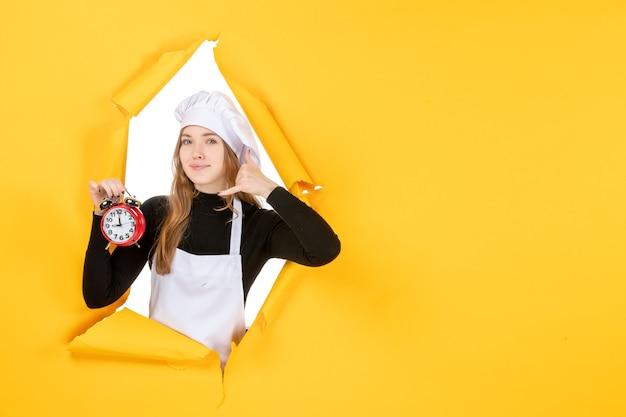 Cuoca vista frontale in berretto bianco cuoco con orologio su foto gialla lavoro cucina cucina cibo sole emozioni
