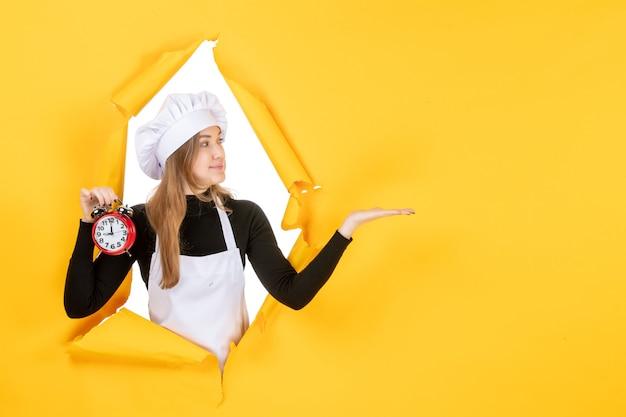 Cuoca vista frontale in berretto bianco da cuoco che tiene orologio su foto gialla lavoro a colori emozione cucina cucina cibo
