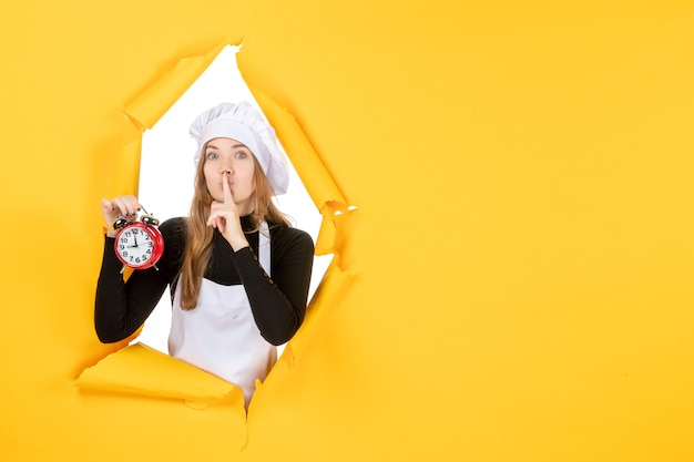 Vista frontale cuoca in berretto bianco da cuoco con orologio su foto gialla lavoro a colori emozione cucina cucina cibo solare
