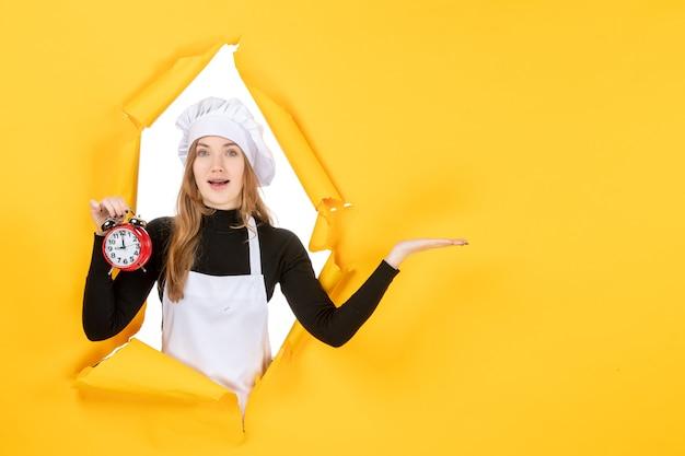 Cuoca vista frontale in berretto da cuoco bianco con orologio su foto gialla lavoro a colori cucina emozione cucina sole