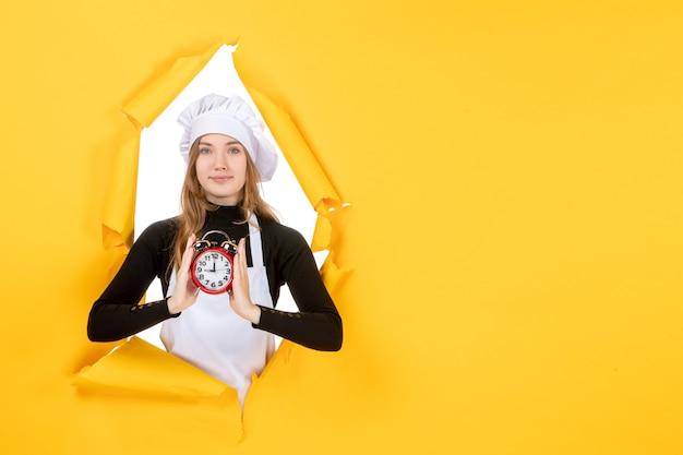 Cuoca vista frontale in berretto bianco cuoco con orologio su foto gialla colori lavoro cucina cucina cibo sole emozione