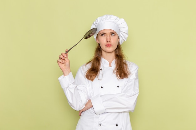 Vista frontale del cuoco femminile in vestito bianco del cuoco che tiene il grande cucchiaio d'argento che pensa sulla parete verde