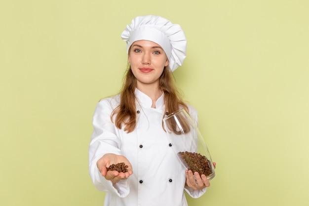 Vista frontale del cuoco femminile in vestito bianco da cuoco che tiene la lattina piena di semi di caffè sulla parete verde chiaro