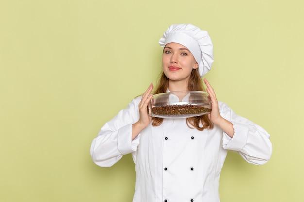 Vista frontale del cuoco femminile in vestito bianco del cuoco che tiene può con i semi di caffè sulla parete verde