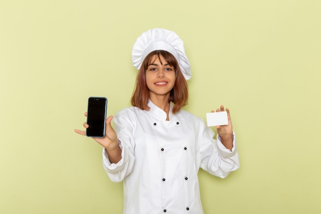 Front view female cook in white cook suit holding card and smartphone on green surface