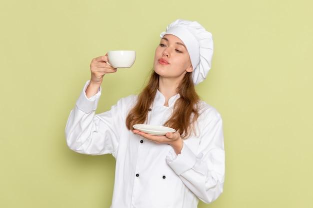 Vista frontale del cuoco femminile in vestito bianco del cuoco che tiene tazza di caffè sulla parete verde