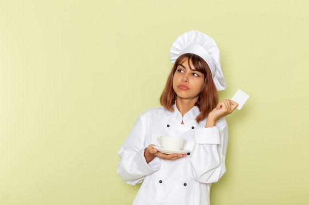 Front view female cook in white cook suit holding cup of tea and card on green desk