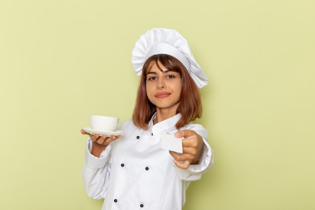 Front view female cook in white cook suit holding cup of tea and card on green surface