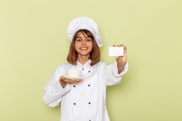 Front view female cook in white cook suit holding cup of tea and card on the green surface