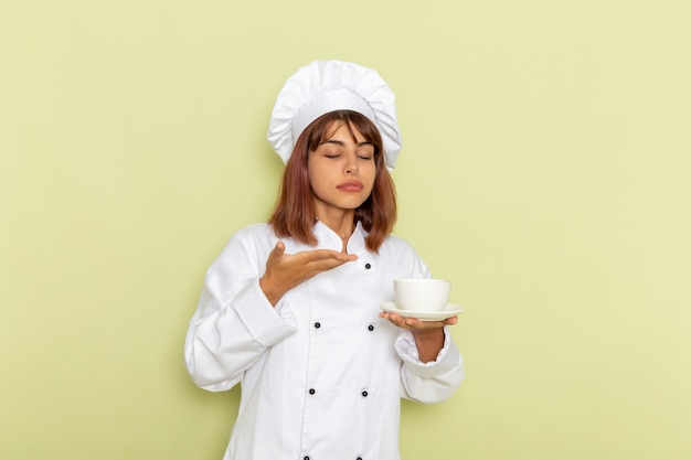 Front view female cook in white cook suit holding cup of tea on a green desk