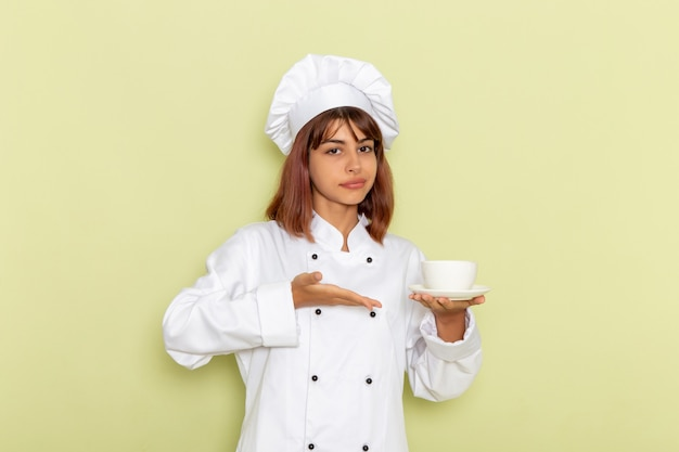Front view female cook in white cook suit holding cup of tea on a green surface