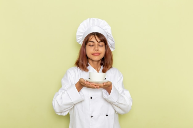 Front view female cook in white cook suit holding cup of tea on a light green surface