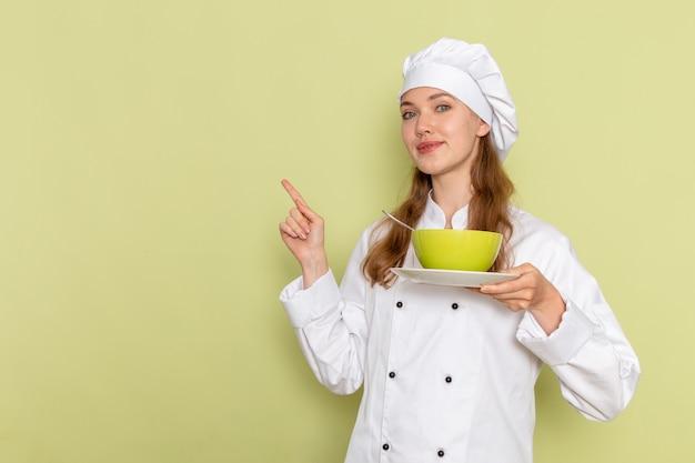 Vista frontale del cuoco femminile in vestito bianco del cuoco che tiene piatto verde sulla parete verde chiaro