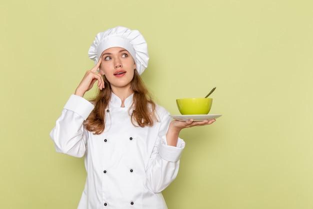 Vista frontale del cuoco femminile in vestito bianco del cuoco che tiene piatto verde con il piatto sulla parete verde