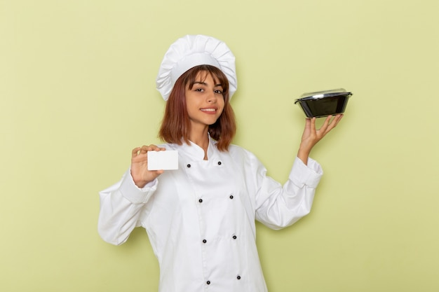 Front view female cook in white cook suit holding white card and bowl on green surface