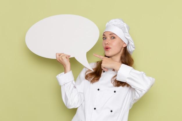 Vista frontale del cuoco femminile in vestito bianco del cuoco che tiene segno bianco sulla parete verde