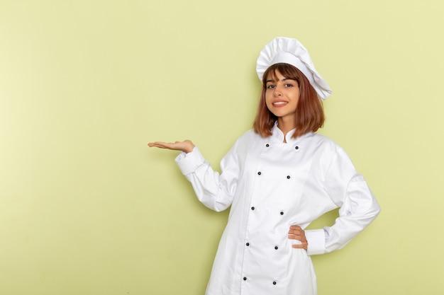 Cuoco femminile di vista frontale in vestito bianco del cuoco che posa sulla superficie verde
