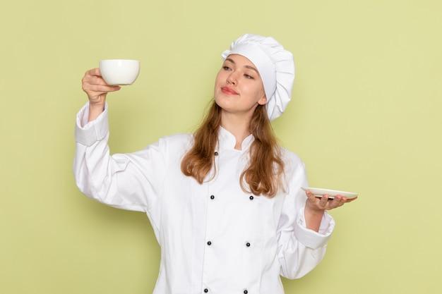 Vista frontale del cuoco femminile in vestito bianco del cuoco che sorride e che tiene tazza bianca con caffè sulla cucina della cucina dello scrittorio verde che cucina colore femminile del pasto