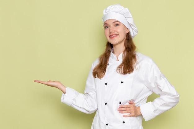 Vista frontale del cuoco femminile in vestito bianco cuoco sorridente in posa sulla parete verde