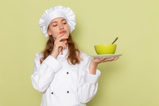 Vista frontale del cuoco femminile in vestito bianco cuoco pensando e tenendo la zolla verde sulla parete verde