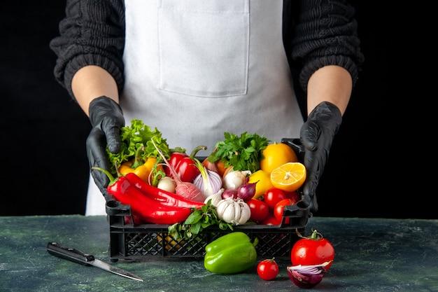 Cuoca vista frontale con cesto pieno di verdure fresche su cibo scuro che cucina cucina di insalata di farina colorata