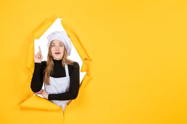 Cuoca vista frontale sul colore giallo sole foto cucina carta emozione cibo lavoro