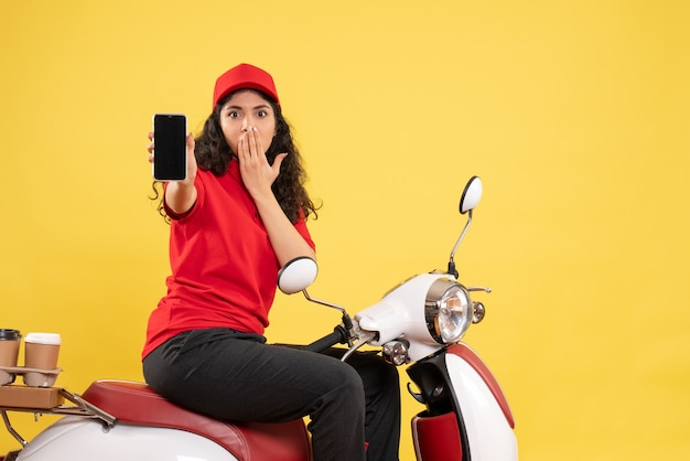 Front view female courier on bike for coffee delivery holding phone on yellow background service delivery uniform job worker work woman