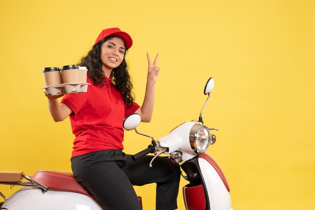 Front view female courier on bike for coffee delivery on a yellow background job service uniform worker woman delivery work