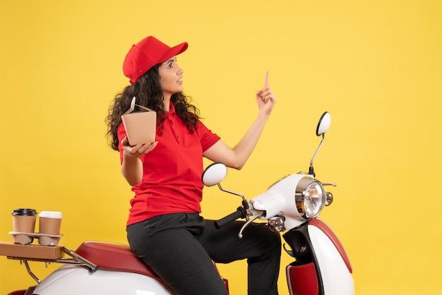 Vista frontale corriere femminile in bicicletta per la consegna di caffè e cibo sullo sfondo giallo servizio di consegna uniforme lavoratore lavoro lavoro donna