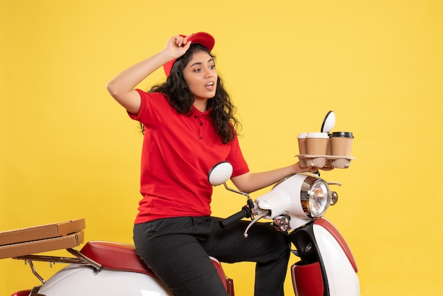 Front view female courier on bike holding coffee cups on yellow background service uniform job woman delivery work