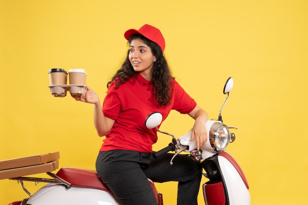Front view female courier on bike holding coffee cups on yellow background worker service job woman delivery work