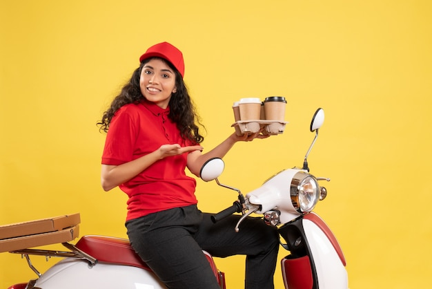 Front view female courier on bike holding coffee cups on yellow background worker service uniform job woman delivery work